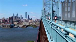 stock-footage-a-group-of-joggers-run-across-the-ben-franklin-bridge-leading-to-philadelphia-pennsylvania